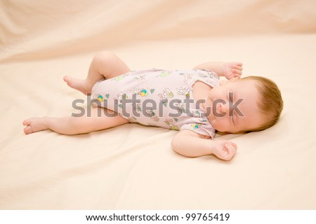newborn wearing a bodysuit, sleeping soundly on his back, stretched hands. - stock photo
