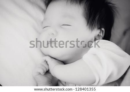 Newborn with dark hair sleeping - stock photo