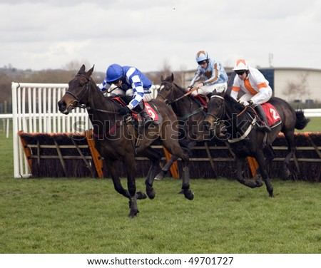 NEWBURY, BERKS - MAR 27: Jockey Aidan Coleman (blue and white) takes lively fling over hurdles in the first race at Newbury Racecourse, UK, March 27, 2010 in Newbury, Berks