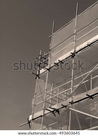 Newbury, Northbrook Street, Berkshire, England - October 03, 2016: Sepia scaffolding with health and safety protection mesh carrying out renovation works over retail units