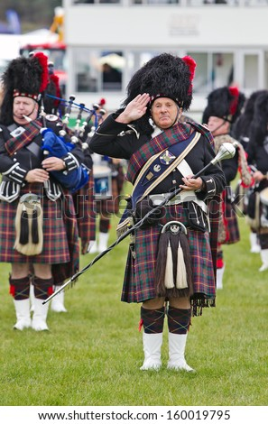 NEWBURY, UK - SEPTEMBER 21: Scottish bagpipers play the popular tune 'Flower of Scotland' to the watching public in the main arena at the Berks County Show on September 21, 2013 in Newbury  - stock photo