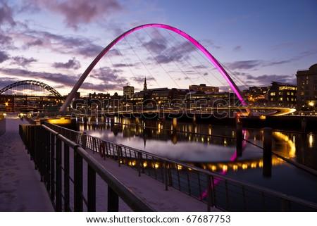 Newcastle at sundown showing Gateshead Millennium Bridge and Tyne Bridges in Winter. - stock photo