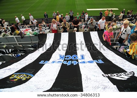 NEWCASTLE UPON TYNE, UK- AUGUST 5:  People gather at a makeshift memorial to Sir Bobby Robson, deceased former England Football Manager, at St James Park stadium on August 5, 2009 in England. - stock photo