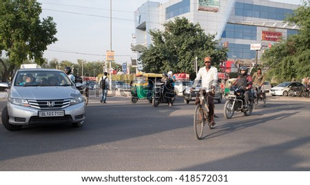 Newdelhi, India - May 06, 2016: Typical volume traffic scene in intersection in Newdelhi. Auto rickshaws and Bus Rapid Transport (BRT) buses provide public transportation.