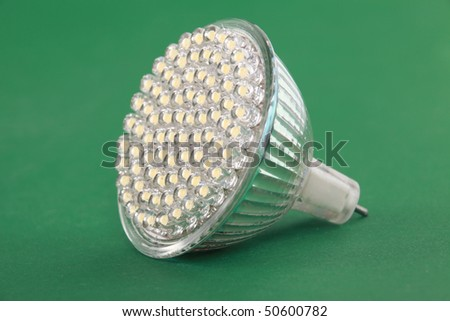 Newest LED light bulb on green background - stock photo