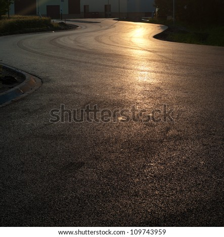newly asphalted road with a sunset reflection - stock photo