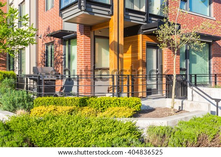 Newly built condos  with nicely trimmed and designed front yard in a residential neighborhood in Canada. Fragment of entrance with barbecue.  - stock photo