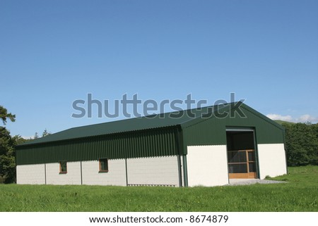 Newly constructed barn of cream painted concrete block walls with a green metal sheet roof,set against a blue sky and trees to the rear. - stock photo