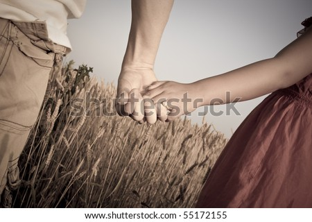 Newly engaged couple holding hands in wheat field. Desaturated for vintage look. - stock photo