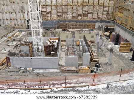 Newly excavated foundation for condo development, with snow - stock photo