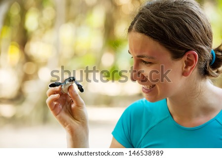 Newly hatched baby turtle in girls hand at Sea Turtles Conservation Research Project in Bentota, Sri Lanka - stock photo