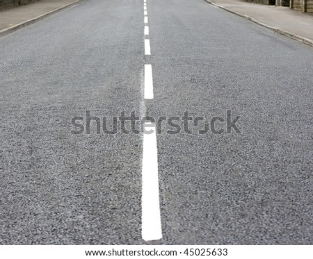 Newly laid tarmac surface of a single lane road
