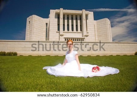 Newly married bride sitting in front of the Cardston Temple. - stock photo