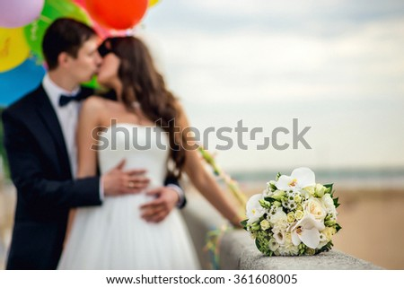 Newly-married couple and wedding bouquet in the foreground. Wedding bouquet with the wedding couple in the background - stock photo