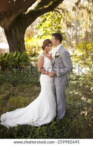 newly married couple having intimate moment in garden, full length portrait - stock photo