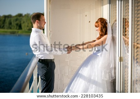 Newly married couple holding hands on deck of cruise liner  - stock photo
