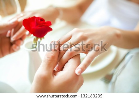 Newly married couple holding hands with rings against wedding dress - stock photo