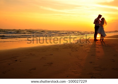 Newly married couple on the ocean with sunset theme - stock photo