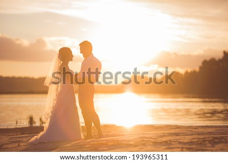 Newly married couple on the river with sunset - stock photo