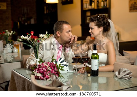 newly married couple sit at table in restaurant,  romance wedding dinner, kiss