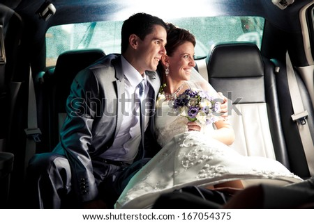 Newly married couple sitting on backseat of the car and looking out of window - stock photo