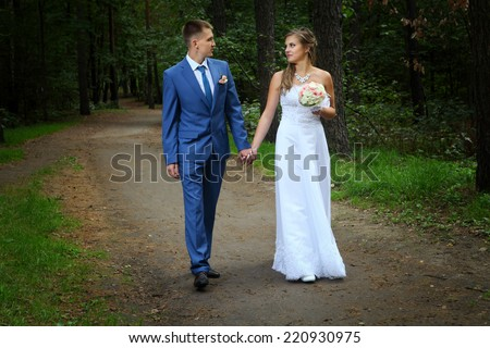 Newly married couple walk on park paths holding hands and looking at each other. - stock photo