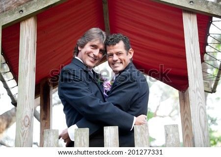 Newly married gay couple embracing under an outdoor canopy.   - stock photo