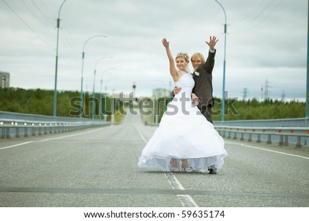 Newly married have fun standing on country highway - stock photo