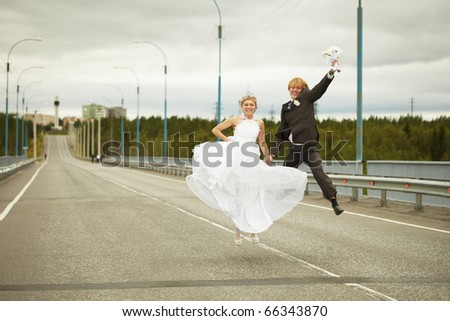 Newly married pair jumps on highway - stock photo