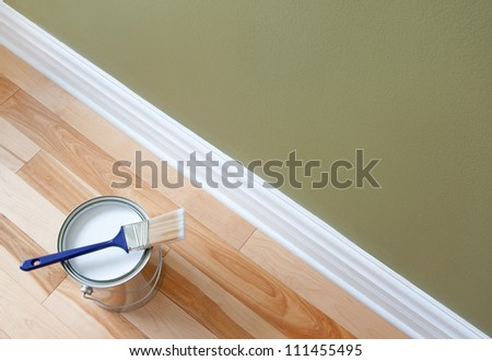 Newly opened can of white paint and paintbrush on wooden floor. - stock photo