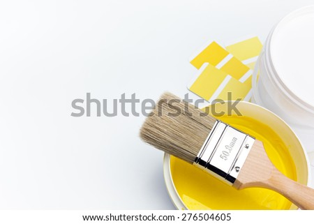 newly opened can of yellow paint and brush with color guide on white background - stock photo