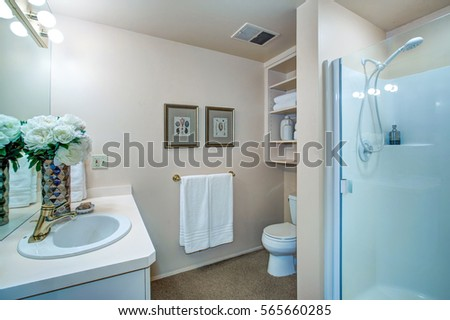 newly remodeled bathroom design with neutral walls showcases white bathroom vanity topped with white countertop framing