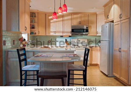 Newly remodeled kitchen interior with cork floors maple cabinets and glass tile backsplash - stock photo