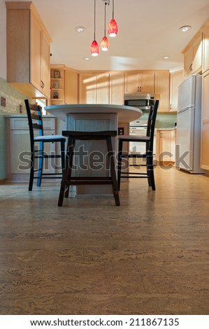 Newly remodeled kitchen interior with cork floors maple cabinets and pendant lights - stock photo