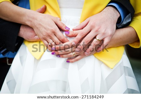 Newly wed couple embracing - focus on hands with wedding rings - stock photo