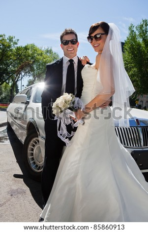 Newly wed couple in sunglasses standing near limousine - stock photo
