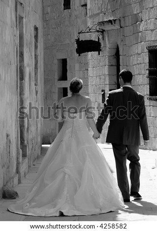 Newly wed couple walking in the old city streets in Malta - stock photo