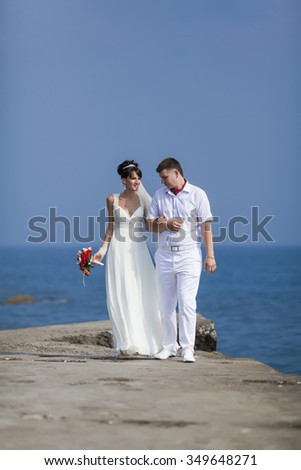 Newly wedded couple on seafront. Just married in day of them wedding walking along seashore - stock photo