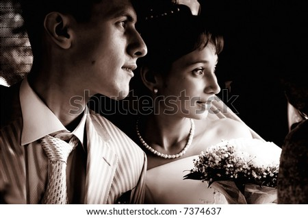 Newly wedded staring into the future from the car - stock photo