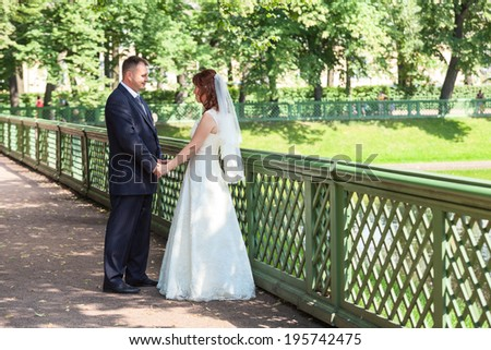 Newly wedding couple walking in garden - stock photo
