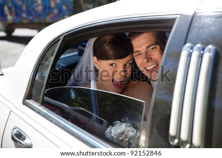 Newly weds laughing in car - stock photo