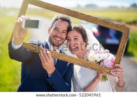 newlywed are going on honeymoon, they take a selfie through an empty frame, they have fun a lot. they are on a country road in the foreground and their car  is blur at the background. Shot with flare