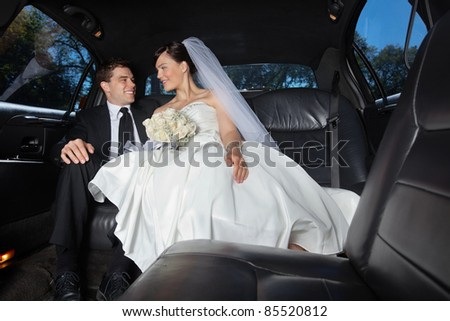 Newlywed bride and bridegroom in car - stock photo