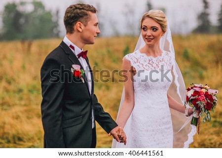 Newlywed bride and groom holding hands in autumn forest field