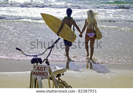 newlywed couple at the beach with surfboards and bikes - stock photo
