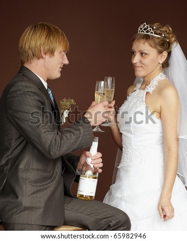 Newlywed couple drinking champagne clinking glasses on brown background - stock photo