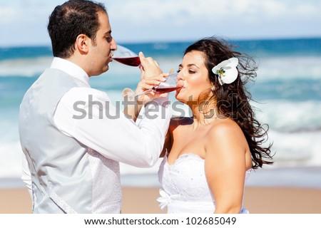 newlywed couple drinking champagne on beach - stock photo