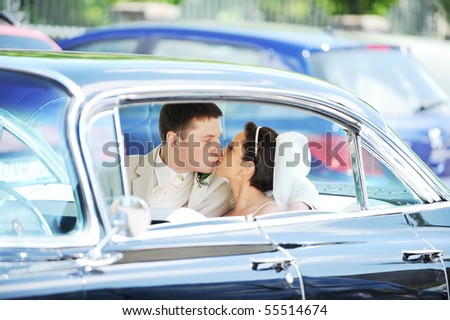 newlywed couple, groom  and bride,  kissing in car - stock photo