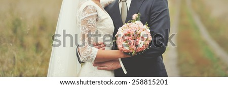 Newlywed couple happy together at field.  - stock photo
