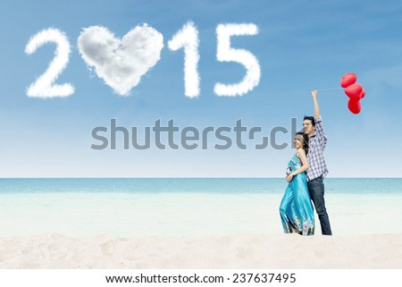 Newlywed couple holding balloon on the beach enjoying honeymoon in new year 2015 - stock photo